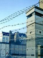 Stacheldraht vor ehemaligem DDR-Wachtturm an der Zimmerstraße in Berlin.